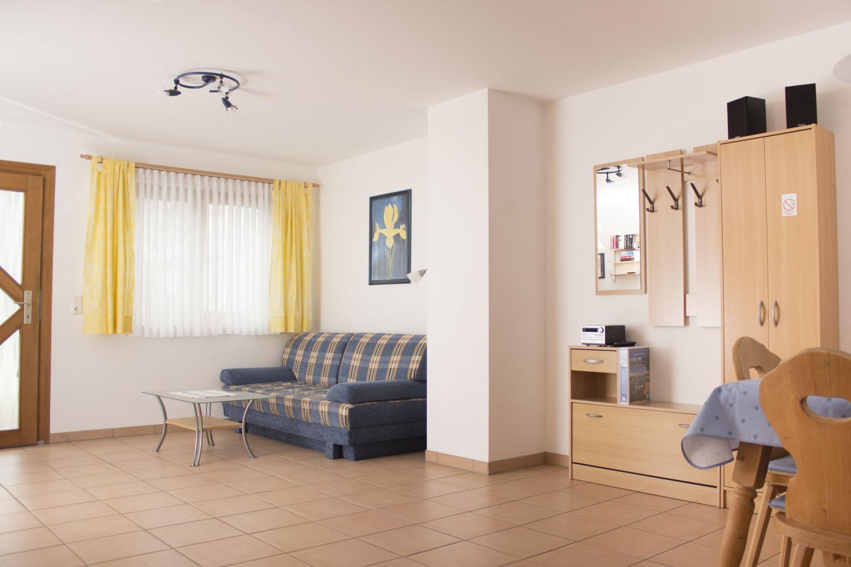 Couch, Garderobe und Esstisch der Ferienwohnung 1